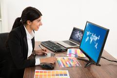 Happy Female Designer Looking At Computer While Using Graphic Tablet At Desk. Stock Photos