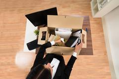 High Angle View Of Businesswoman Packing Personal Belonging In Box - stock photo