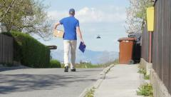 Slow motion of a delivery guy with box walking down the street Stock Footage