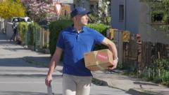 Delivery guy walking and searching address Stock Footage