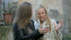 Happy daughter shows to her mother a photo on her mobile phone Stock Footage