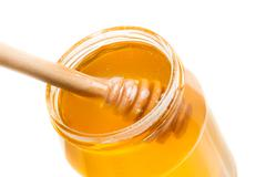 opened honey jar on white background with wooden honey dipper inside - stock photo