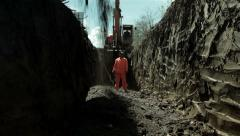 Excavator spilling gravel in the canal, low angle view, construction site. Stock Footage