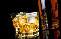 whiskey with ice in glasses near bottle on black background - stock photo