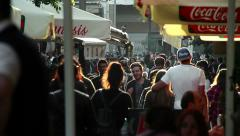 people walking in the city in a summer sunset: crowd walking, restaurant, shops - stock footage