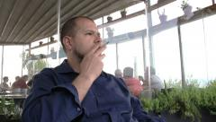 Stock Video Footage of young pensive man smoking at the restaurant: addicted, cancer, bad habits