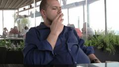 Man smoking sitting in a cafe: cancer, addiction, restaurant Stock Footage
