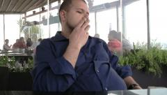 man smoking in a cafe: ash, addiction, cancer, bad habits, nervous, waiting - stock footage