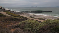 wide shot of the US Mexico Border fence where it heads into the Pacific - stock footage