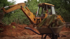 JCB Bulldozer tractor digging soil with Indian worker carrying wheelbarrow 3 Stock Footage