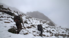 Cloudy mountain side with hunters. Stock Footage