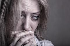Young sad girl crying on a dark background - stock photo