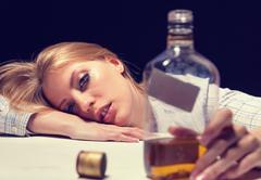 Young beautiful woman in depression, drinking alcohol Stock Photos