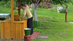 Worker draw full bucket water from wooden country well Stock Footage