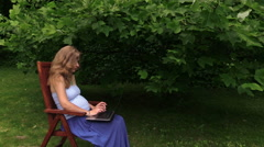 Pregnant girl work with laptop sit in chair near tulip tree. Stock Footage