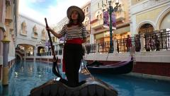 Girl gondolier steers the boat and sings, Venetian. Macao. Stock Footage