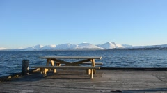 Wooden bench on pier with snowy mountain, blue fjord and sky Stock Footage