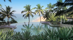 The pool on the edge of the rock overlooking the ocean and palm trees Stock Footage