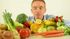 man smells to healthy food - vegetables and fruits - white background studio - stock footage