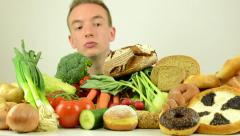 Man looks on food - food - vegetables, fruits and bakery products - studio Stock Footage