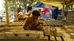 Indian boy glazing cement blocks in a workshop. Stock Footage