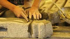 Indian boy applying glaze with his fingers on a cement block. Stock Footage