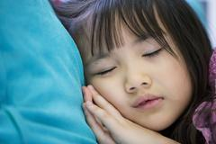 Adorable little girl sleeping in a bed Stock Photos