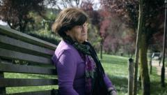 Sad and depressed old woman on the park bench Stock Footage