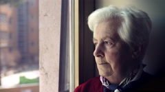 Sad anxious old woman open and close eyes, looks out the window Stock Footage