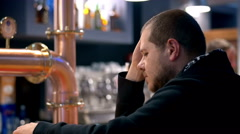 Depressed and sad man drinking whisky at the counter of a pub Stock Footage