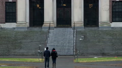 Two college students in front of Harvard library Stock Footage