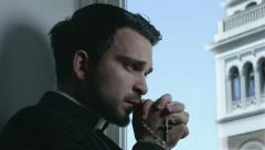 Priest prays with a rosary in his hand and bell tower in background Stock Footage