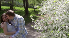 Loving couple walking in a park near a blossoming tree Stock Footage