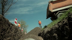 Dump truck spilling ground,backfilled concrete pipes,low angle,construction work Stock Footage