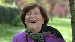 happy old woman smiling and laughing to the camera - stock footage