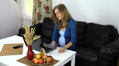 Pregnant woman work computer at home, eat red ripe apple Stock Footage