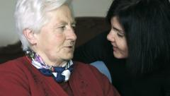 Old woman and her daughter talking sitted on the bed Stock Footage