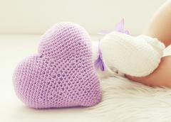 Knitted heart and legs baby in white bootees Stock Photos