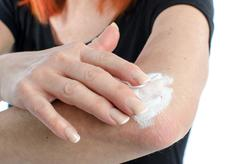 Woman putting cream on her elbow - stock photo