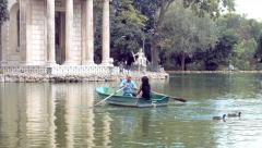 Lovers taking a tour with a rowboat in villa Borghese in Rome Stock Footage