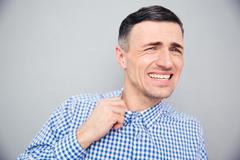 Annoyed man loosing his shirt to relax a bit after hard work - stock photo