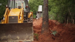 JCB Bulldozer tractor digging soil with Indian worker in background 2 Stock Footage