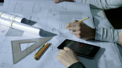 Team of architect working on blueprint with square ruler and calculator Stock Footage