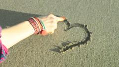 Draw a heart sign on a sand Stock Footage