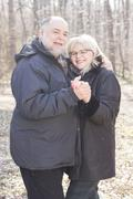 Happy Elderly Senior Romantic Couple holding hands in nature, Old people port - stock photo