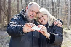 Happy Senior Elderly Couple taking Selfie with phone outdoor.Old people portr - stock photo