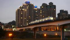 Train moving ahead on overpass bridge against night buildings - stock footage