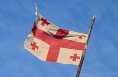 Old georgian national flag with red crosses and the blue sky Stock Photos