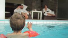 Kid greeting parents in the swimming pool - stock footage