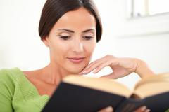 Head and shoulders portrait of a peaceful woman with brown hair reading a boo - stock photo
